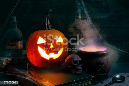 Carved pumpkin Halloween decoration covered in spider webs and cauldron with smoke.