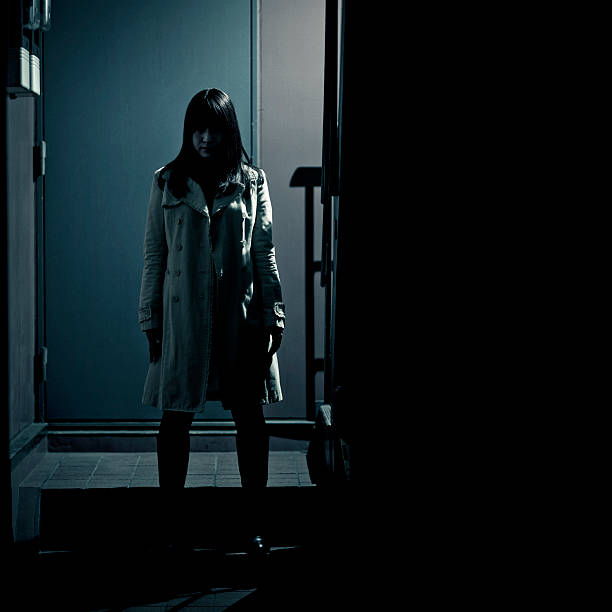 spooky japanese girl at the entrance of building stalker/spy/criminal - spooky scene were a japanese girl wearing a light colored coat appears to be waiting in the dark at the entrance of a modern building in tokyo creepy stalker stock pictures, royalty-free photos & images