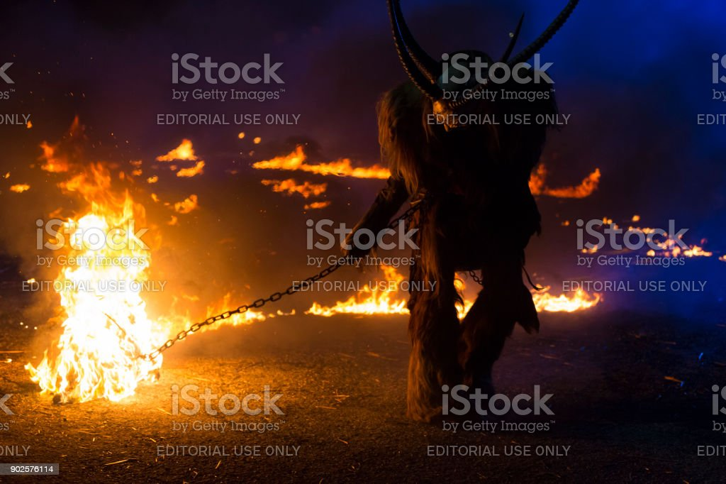 Spooky Krampus character dragging fire chain stock photo