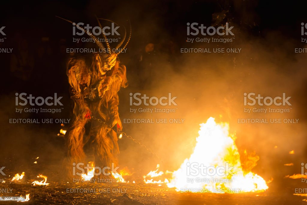Spooky Krampus character stirring the fire stock photo