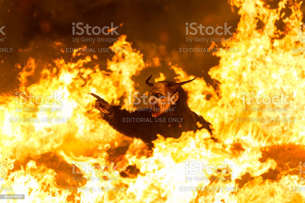 Spooky Krampus in the fire  pointing at misbehaved children stock photo