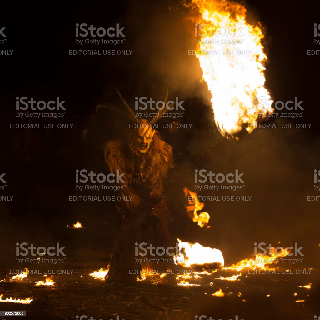 Spooky Krampus running about with a flaming torch stock photo