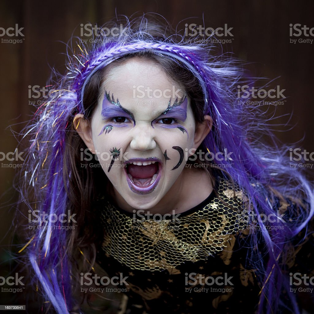 Spooky little witch roaring and facing the camera royalty-free stock photo