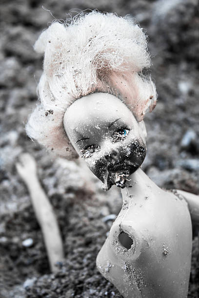 spooky plastic doll on the pile of ash - ash cross stock photos and pictures