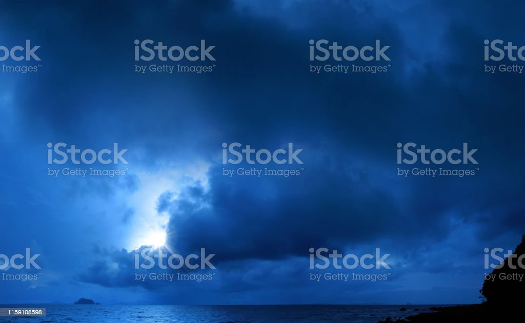 spooky seascape image of dark sky with storm clouds and shining sun...