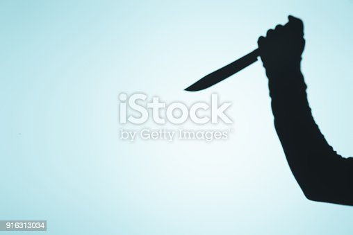istock spooky shadow of person holding knife in hand on blue 916313034