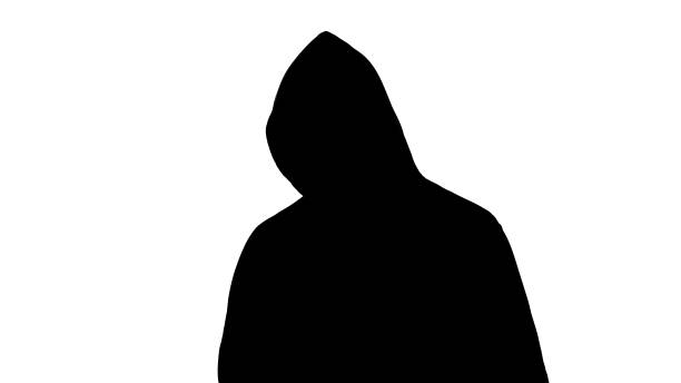 Spooky silhouette in hoodie posing before camera, terror and criminal, fear Spooky silhouette in hoodie posing before camera, terror and criminal, fear stranger stock pictures, royalty-free photos & images