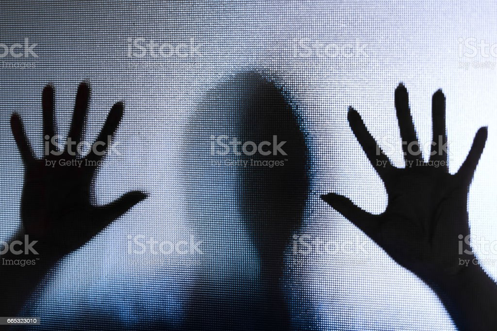 Spooky silhouette of woman with hands pressed against glass window stock photo