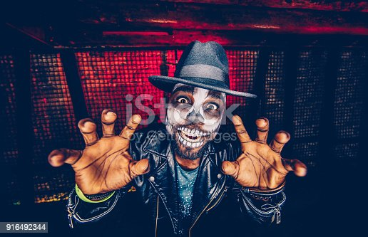 Portrait of young man disguised as scary skeleton skull having fun at Halloween party