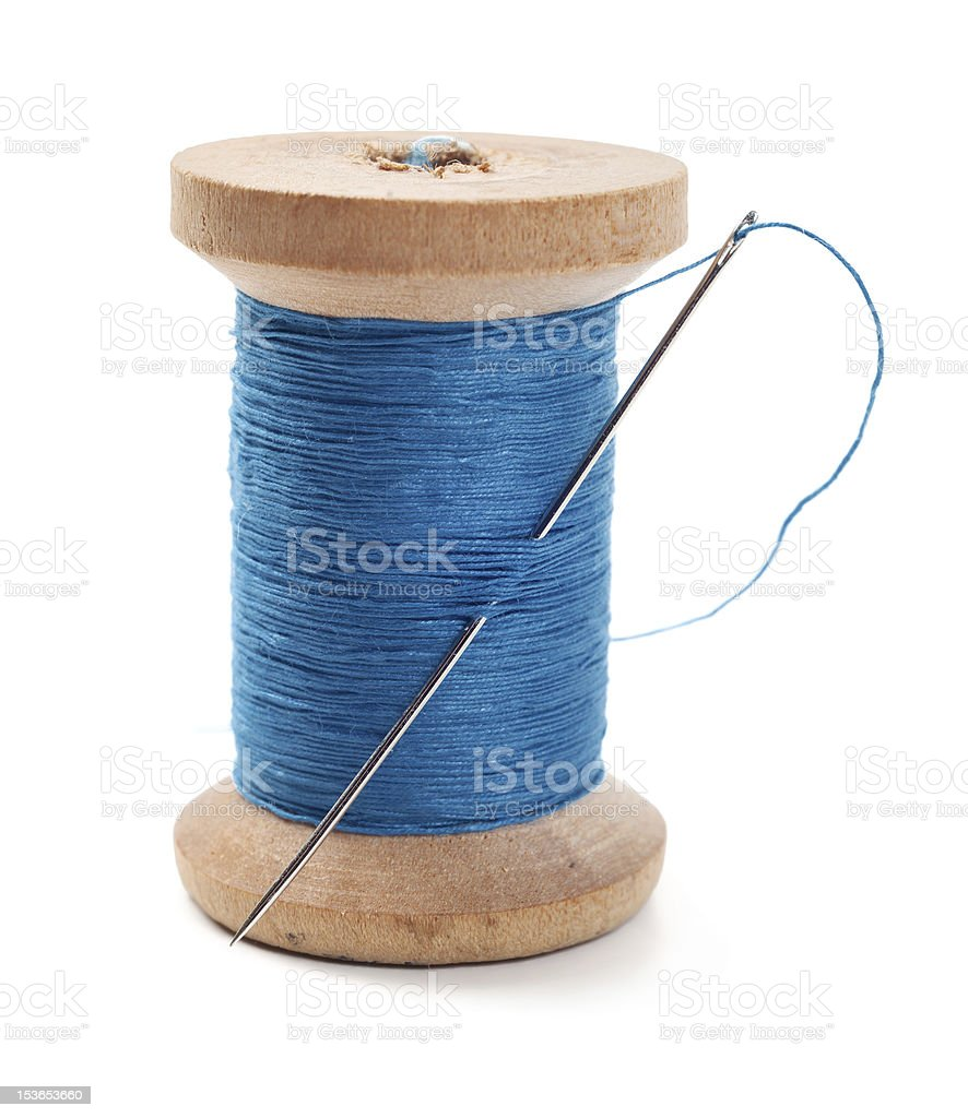 A spool of blue thread with a needle in it stock photo