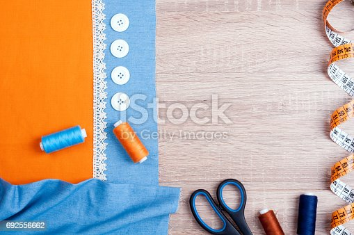 istock Spool of thread, jeans and cotton fabrics for sewing, lace, measuring tape, scissors, buttons and accessories for needlework on old wooden background. Set for needlework top view 692556662