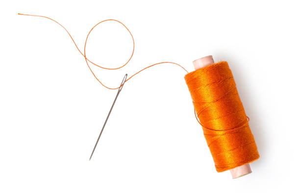 spool of thread with a needle spool of thread with a needle on white isolated background sewing needle stock pictures, royalty-free photos & images