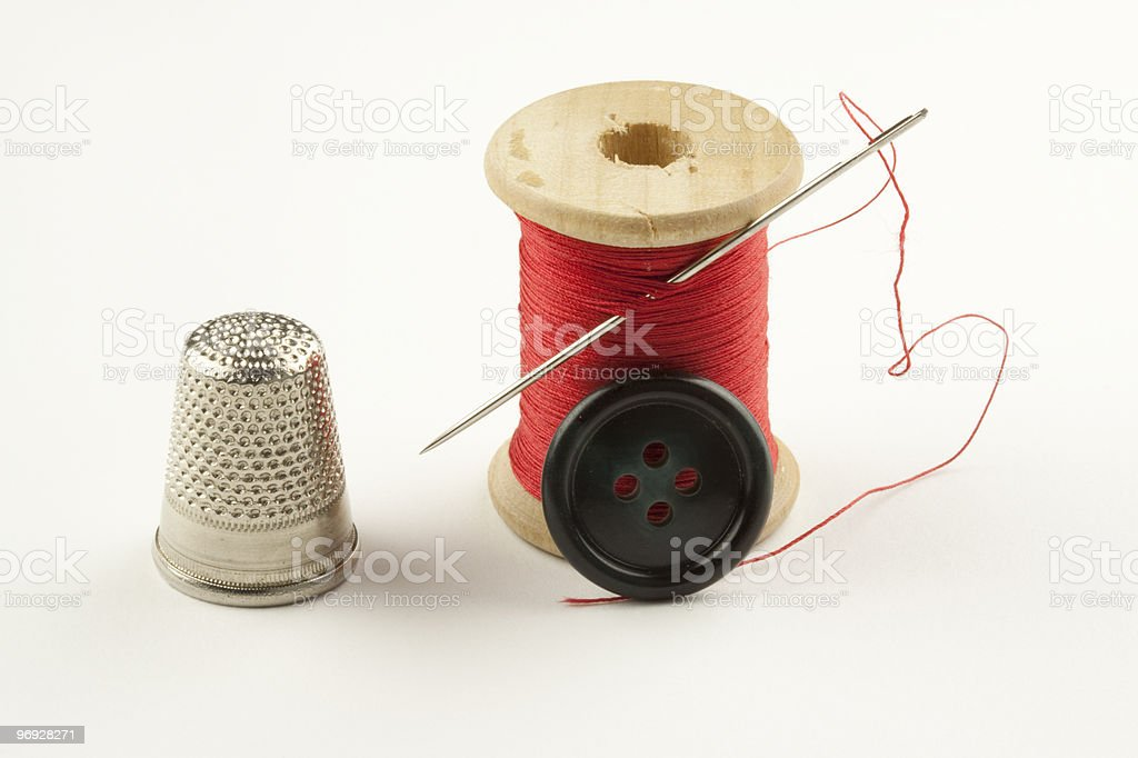 Spool with Thread, Thimble, Button and Needle royalty-free stock photo