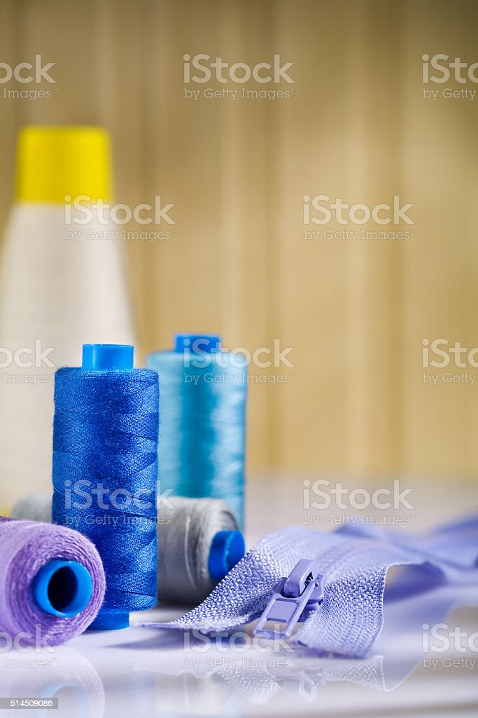 spools and zip on white table stock photo