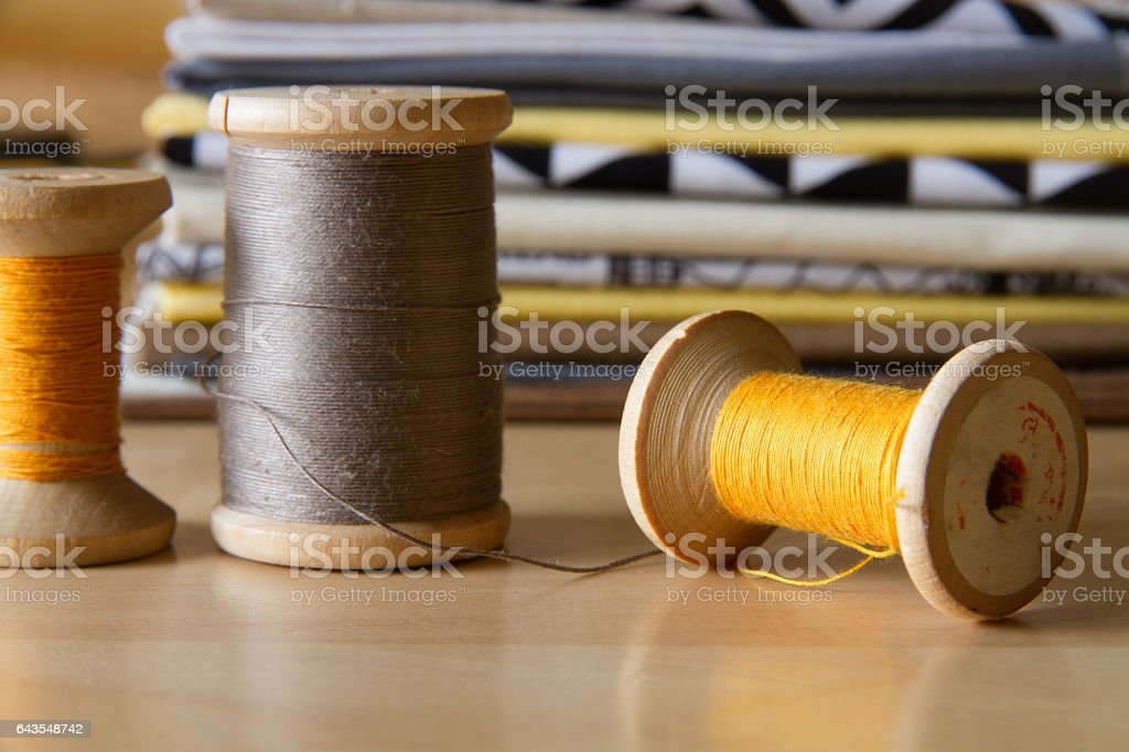 Spools in front of cotton fabrics stack стоковое фото