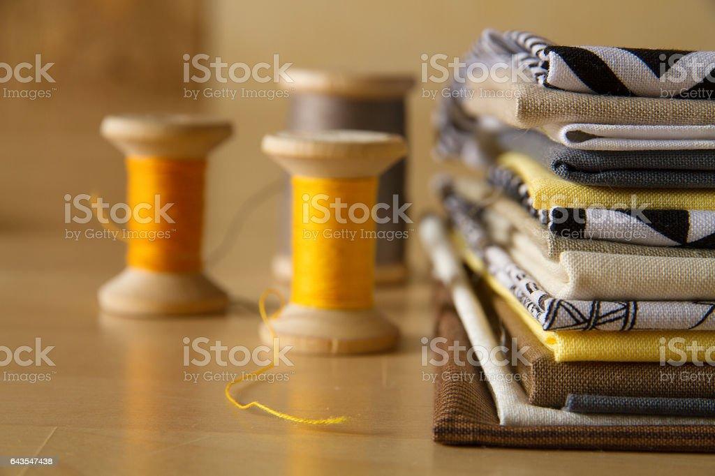 Spools near stack of cotton fabrics стоковое фото