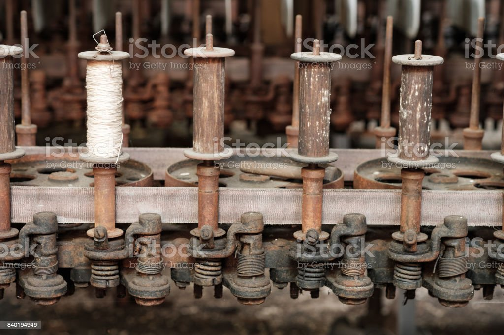 Spools of silk and thread sit on the spindles of heavy duty antiquated and obsolete manufacting equipment in an abandoned old mill stock photo