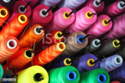 vibrant close up photograph of a group of brightly colored spools of threads