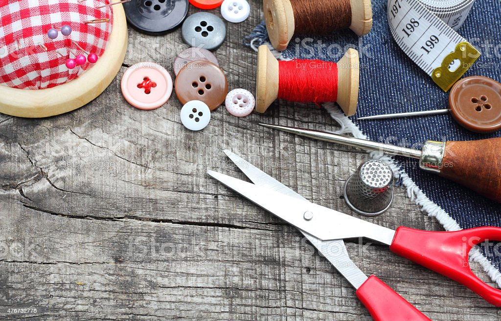 Spools of threads buttons needle for sewing vintage retro style stock photo