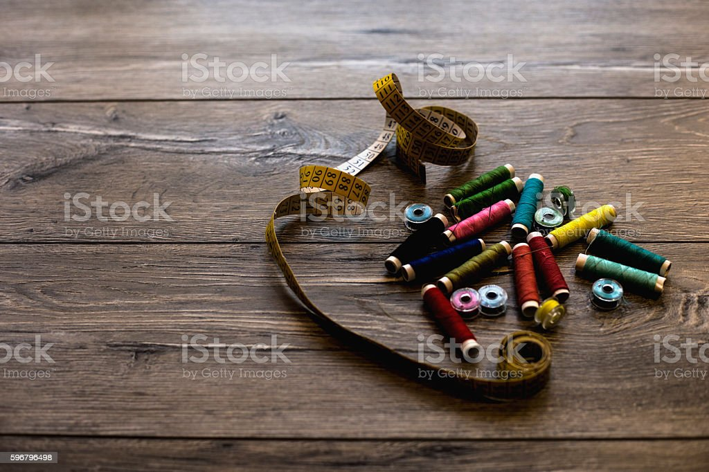Spools with various colors of thread on dark background. stock photo