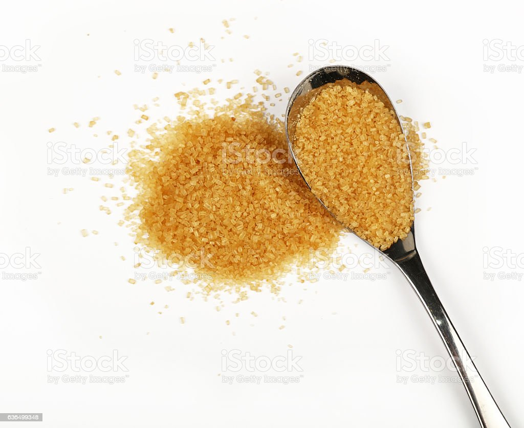 Spoon and pinch of brown cane sugar on white stock photo