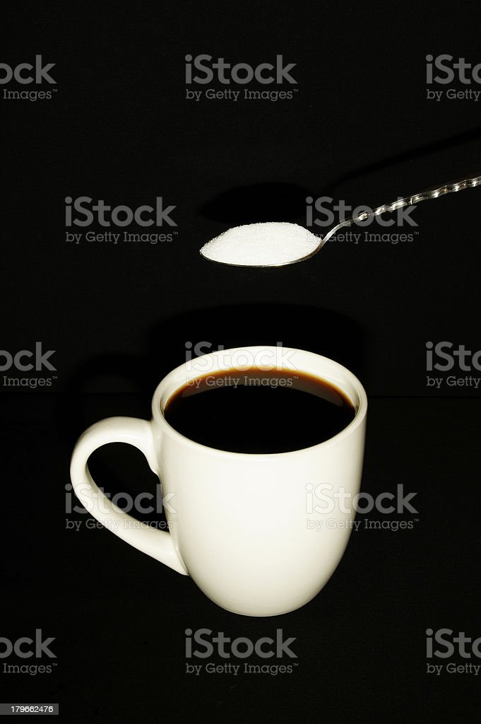 Spoon and Sugar Hovering Over Mug Full of Coffee Portrait royalty-free stock photo