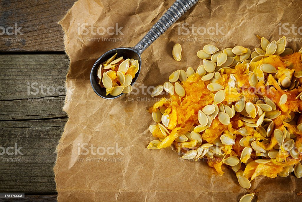 Spoon Filled With Pumpkin Seeds On Brown Paper royalty-free stock photo