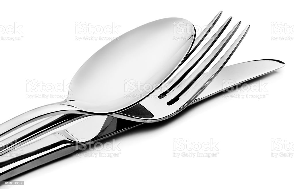 Spoon, fork and knife stacked up on a white background stock photo