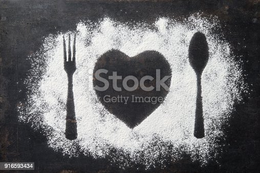Spoon, Fork and plate in heart shape, flour sprinkled around the dark table