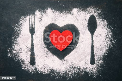 Spoon, fork and plate with red heart, flour sprinkled around the dark table