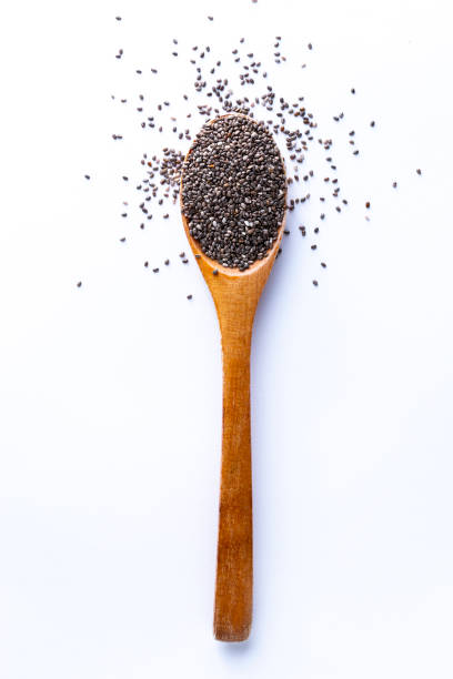 spoon full of chia grains on white background - chia seed stock photos and pictures