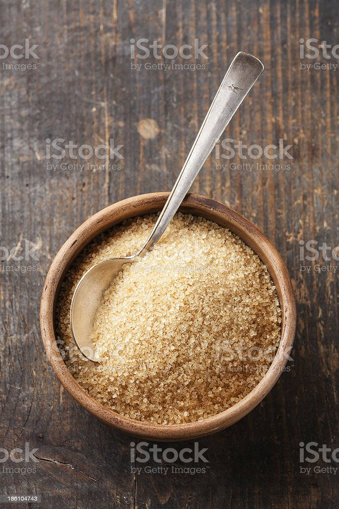Spoon in wooden bowl of brown sugar stock photo