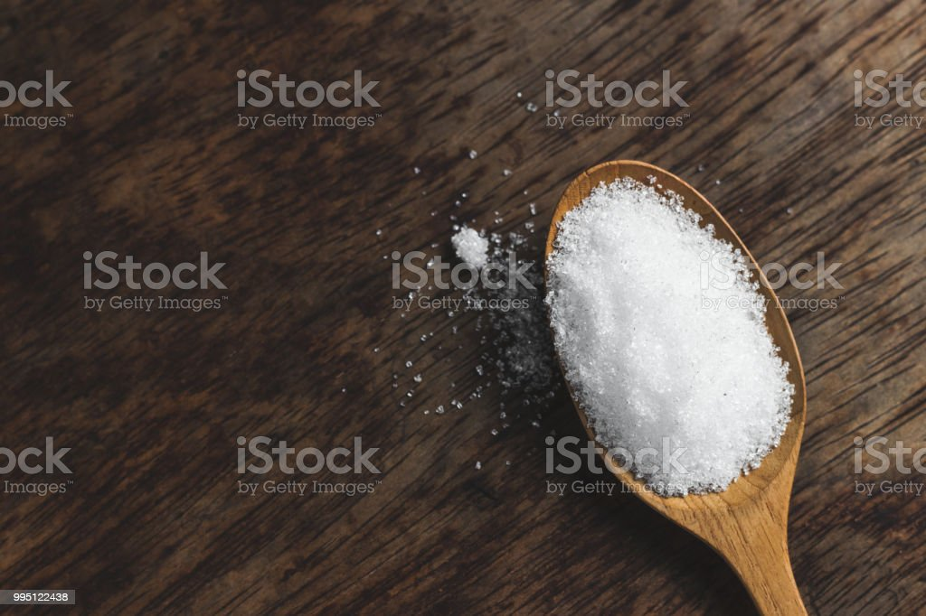 Spoon of fine granulated sugar on wood table. stock photo