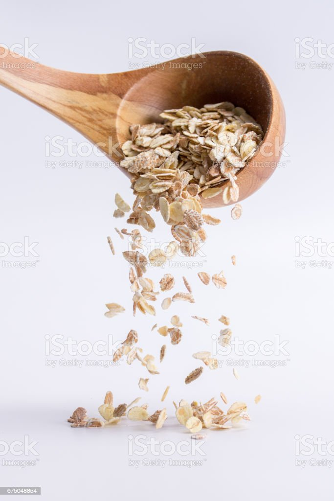 Spoon of oatmeal falling on a white background stock photo