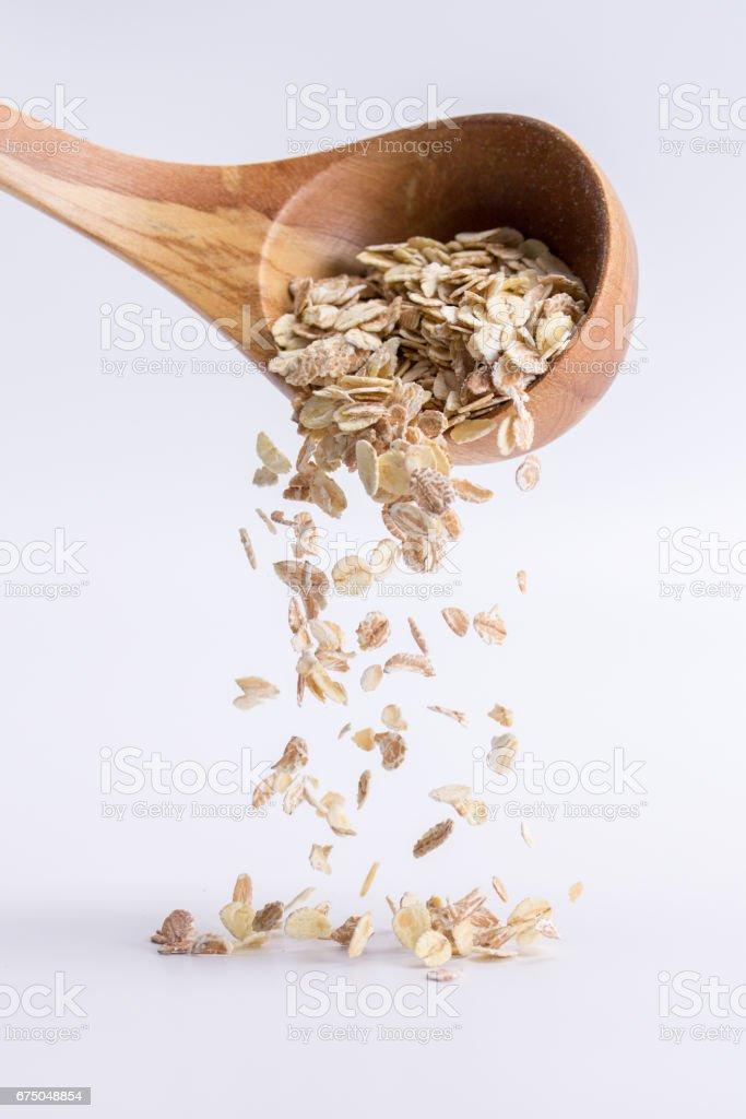 Cuillère de farine d'avoine tombant sur un fond blanc - Photo