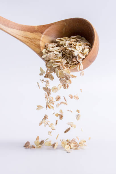 Spoon of oatmeal falling on a white background - foto stock