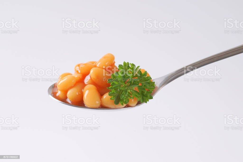 spoon of of beans in tomato stock photo