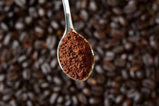spoon of powder coffee with beans in background - café solúvel imagens e fotografias de stock