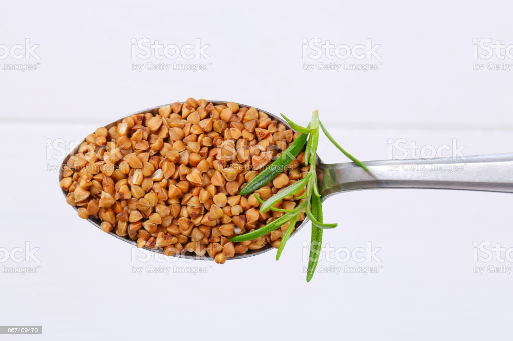 spoon of raw buckwheat stock photo