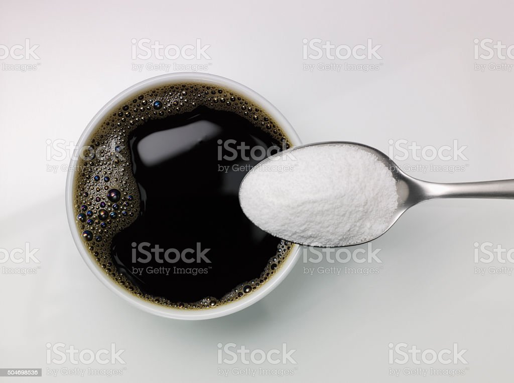 Spoon of sugar above a cup of coffee stock photo