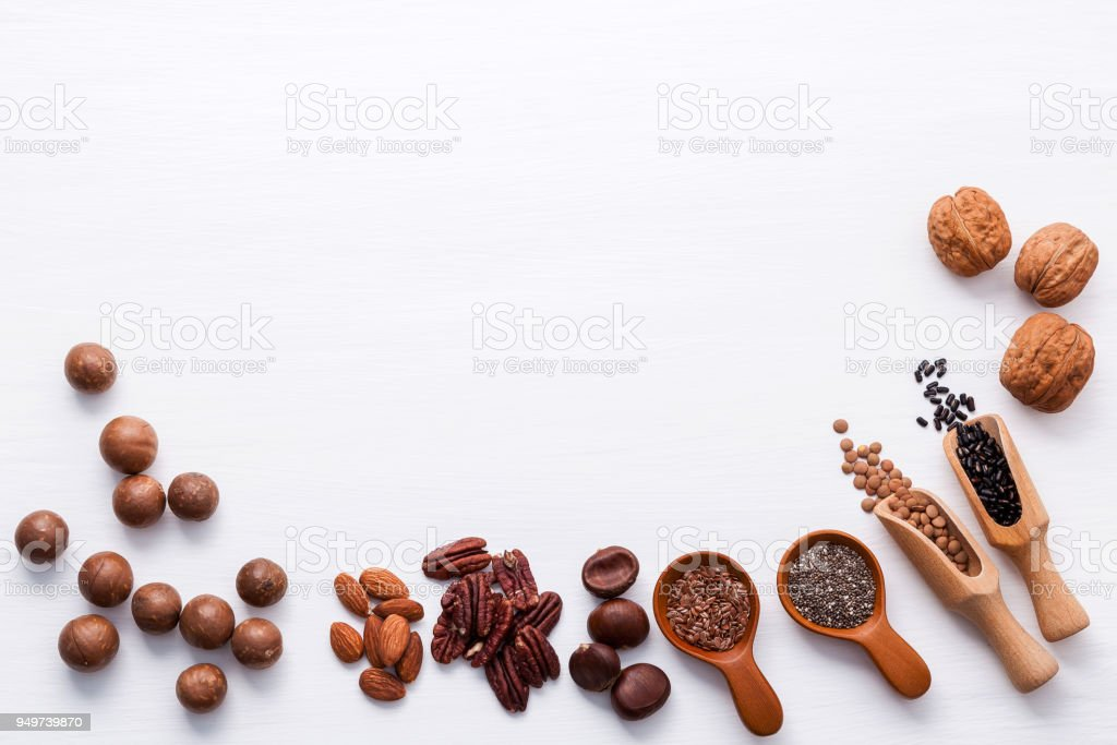 Spoon of various legumes and different kinds of nuts walnuts kernels ,hazelnuts, macadamia ,almond kernels,brown pinto ,red kidney beans and pecan set up on white wooden table. stock photo