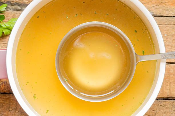 Cuillère avec bouillon à la poêle avec un bouillon d'arrière-plan - Photo