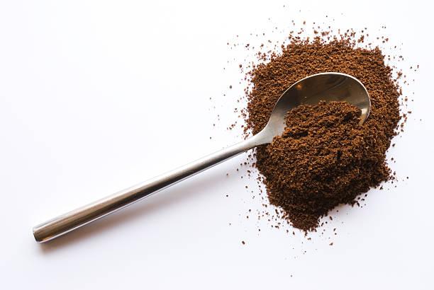 löffel mit kaffee auf weißem hintergrund - kaffeepulver stock-fotos und bilder