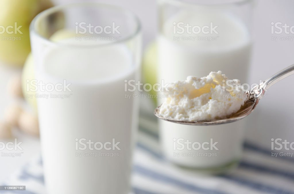 Closeup of organic cottage cheese in spoon against of glasses of milk...