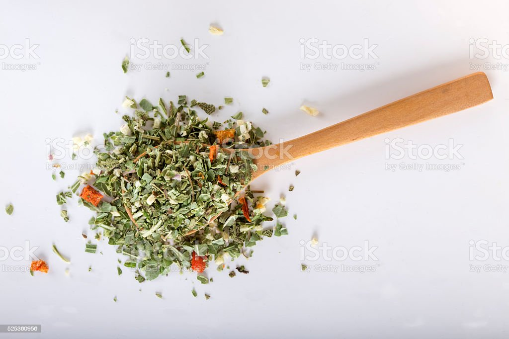 Spoon with dried oregano and thyme, basil and vegetables stock photo