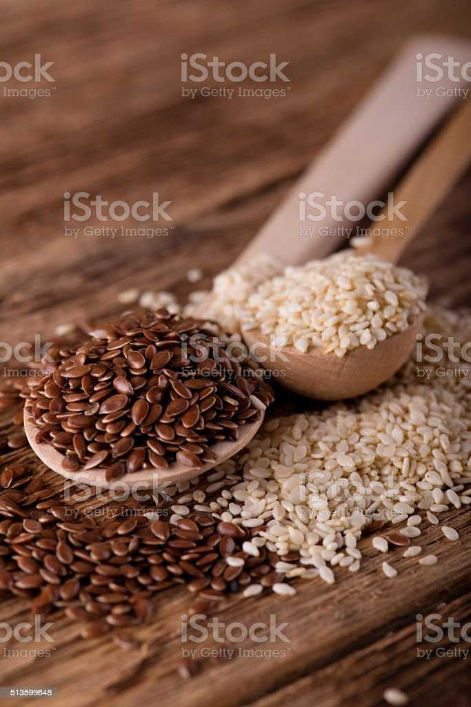 Spoon with flux seeds next to second with sesame stock photo