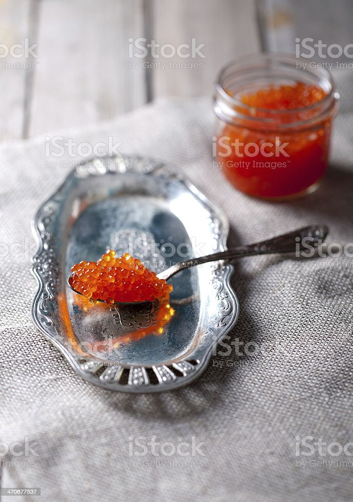 Spoon with salmon red caviar on a silver vintage plate royalty-free stock photo