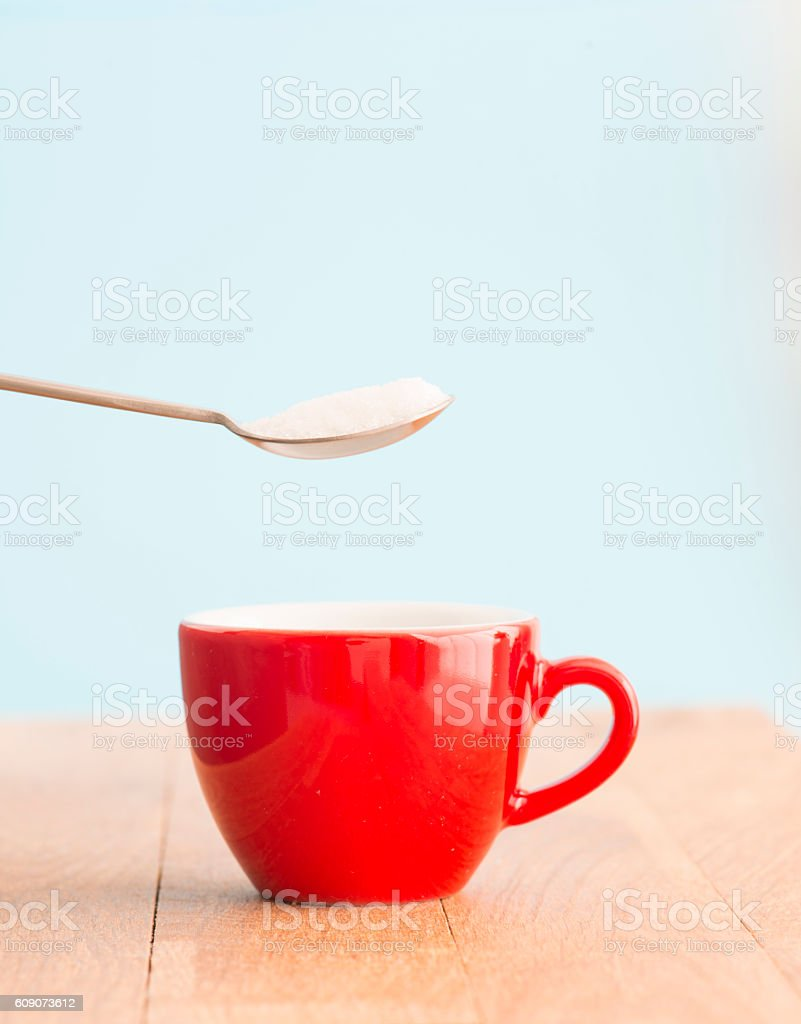 Spoon with sugar and cup stock photo