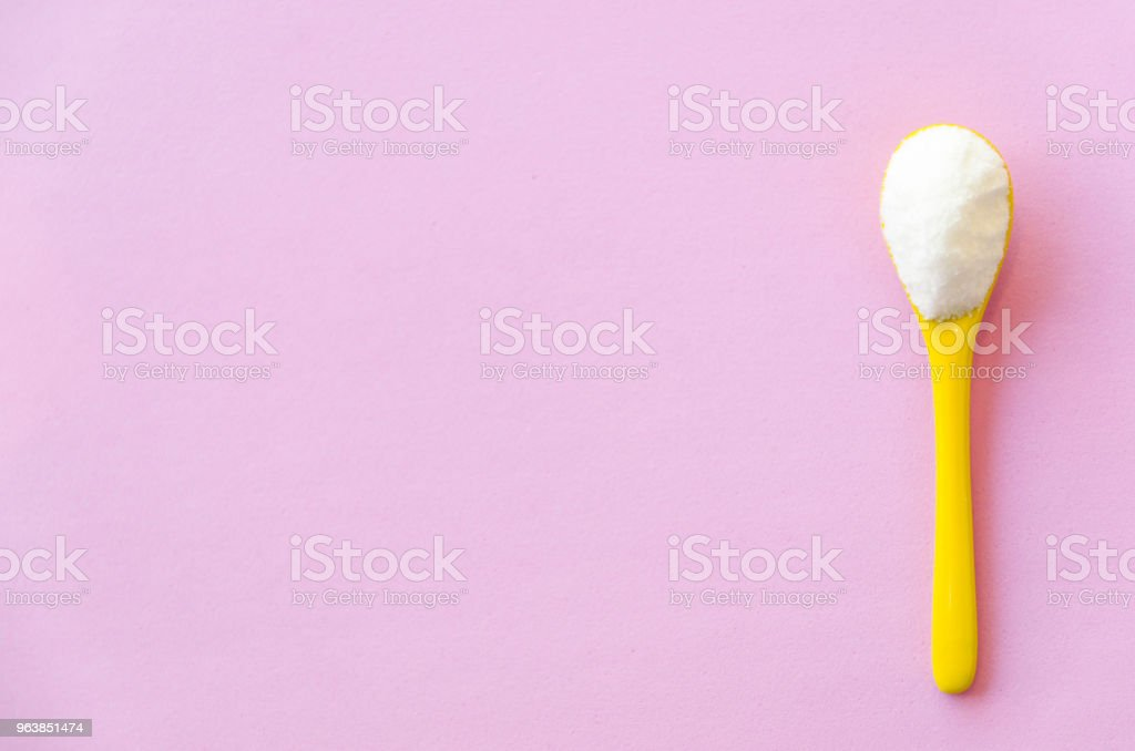 Spoon with sugar close-up on a pink background stock photo