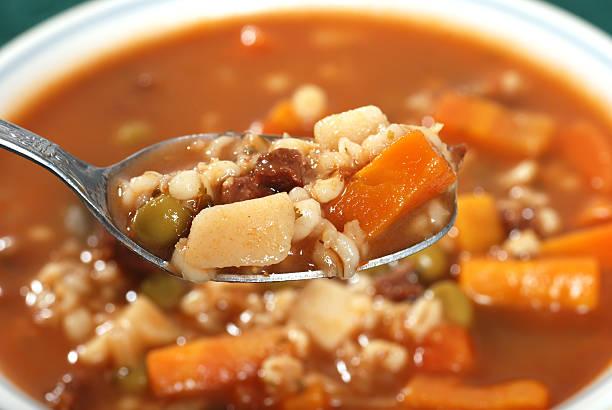 spoonful of beef barley soup stock photo